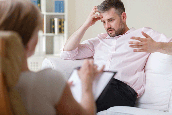 sober business man seeing addiction therapist for motivational interviewing