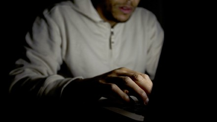 Man on laptop at night, concept of technology addiction