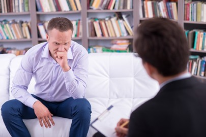 Depressed man talking to his psychologist about addiction