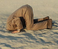 image of man with head buried in sand to symbolize avoidance