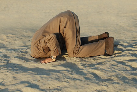 image of a man with head in sand to symbolize avoidance